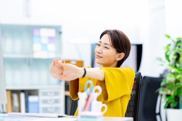 仕事の合間にストレッチをする女性
